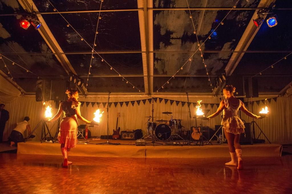 Fire dancers stand beneath clear roof panels, ready to perform on the parquet dancefloor