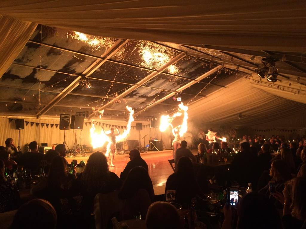 The light from the fire dancers looks incredible reflecting of the clear roof panels at this Bristol marquee event