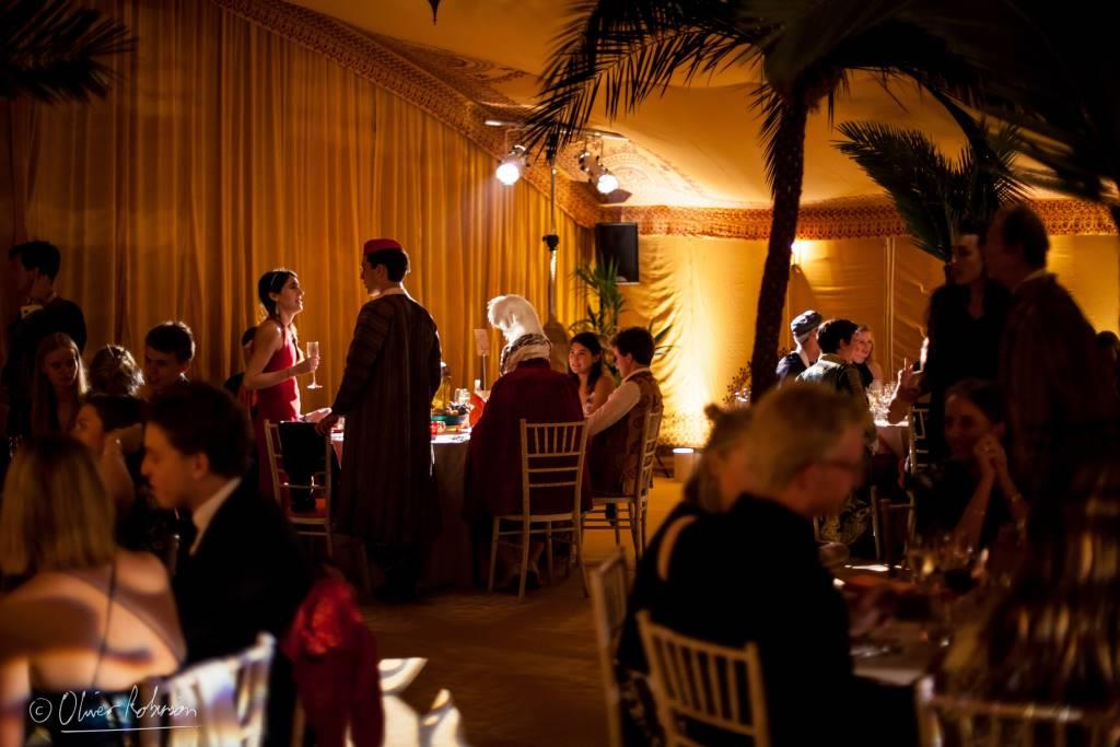 Guests within a silk road inspired party marquee with saffron linings