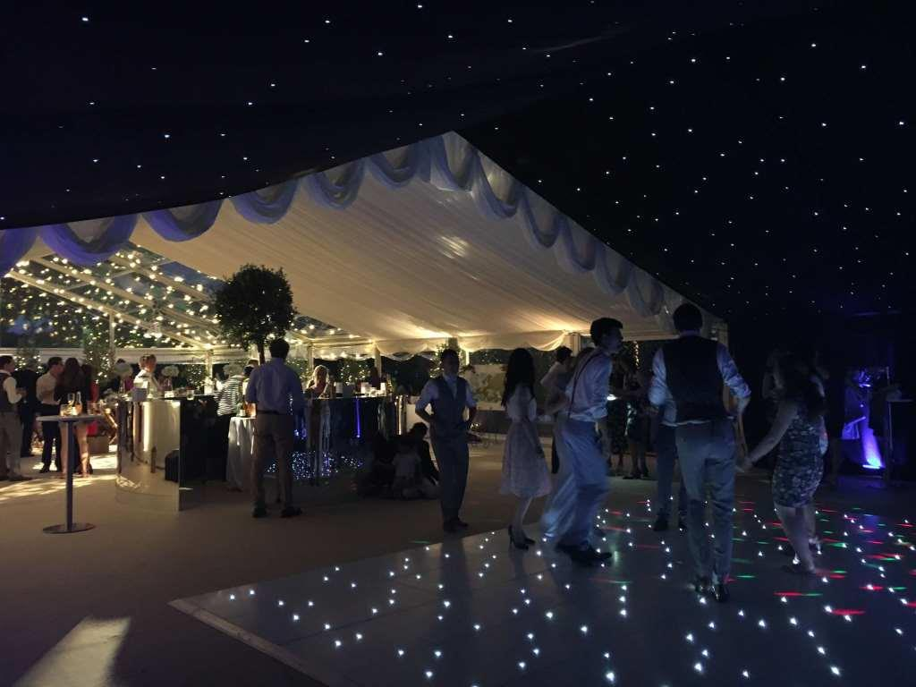 Star cloth roof linings, ivory pleated linings and clear roofs create separate area at this wedding marquee in Bristol