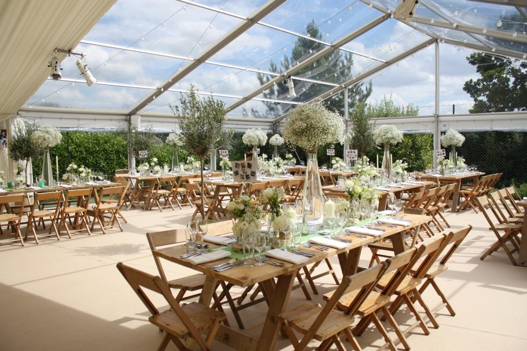 Vintage trestle tables and vintage chairs beneath clear roofs for a stylish wedding in the South west