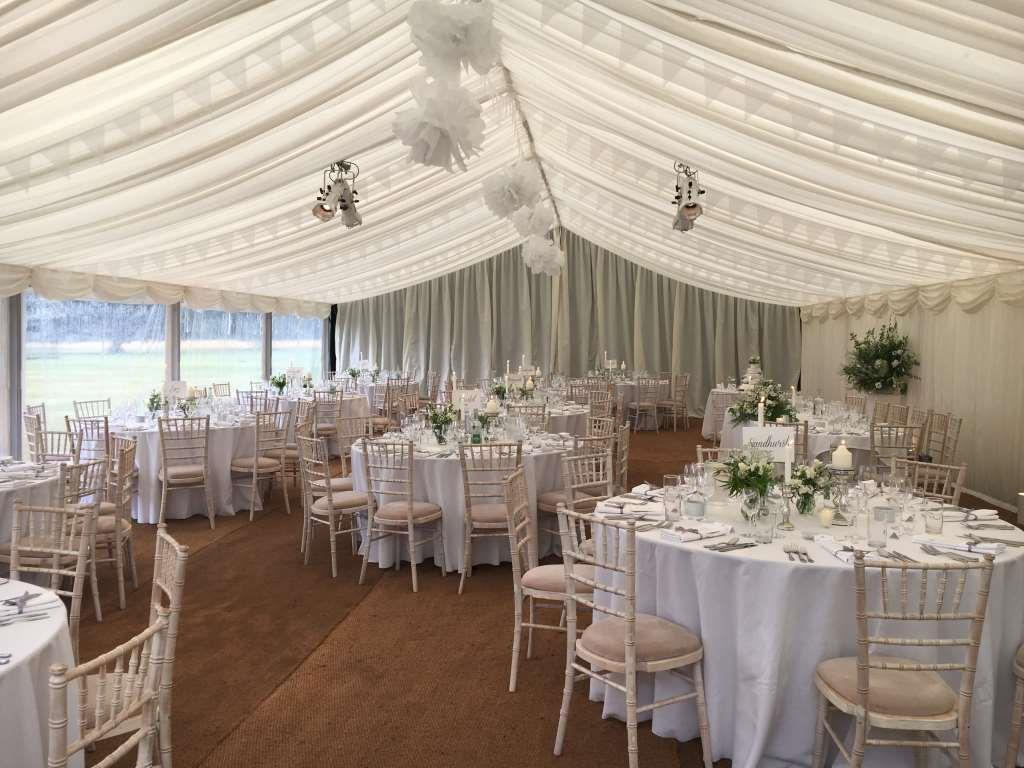 Window walls, ivory pleated linings, Chiavari chairs and round tables