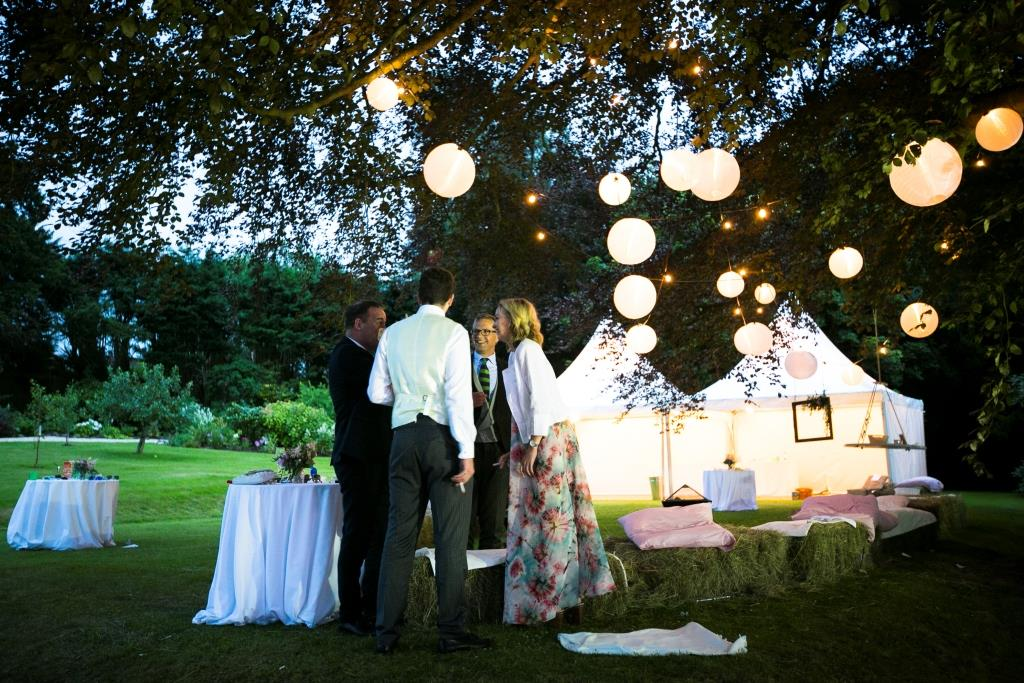 Hanging lanterns and hay bails for a stunning chill out area at this marquee wedding in Bristol