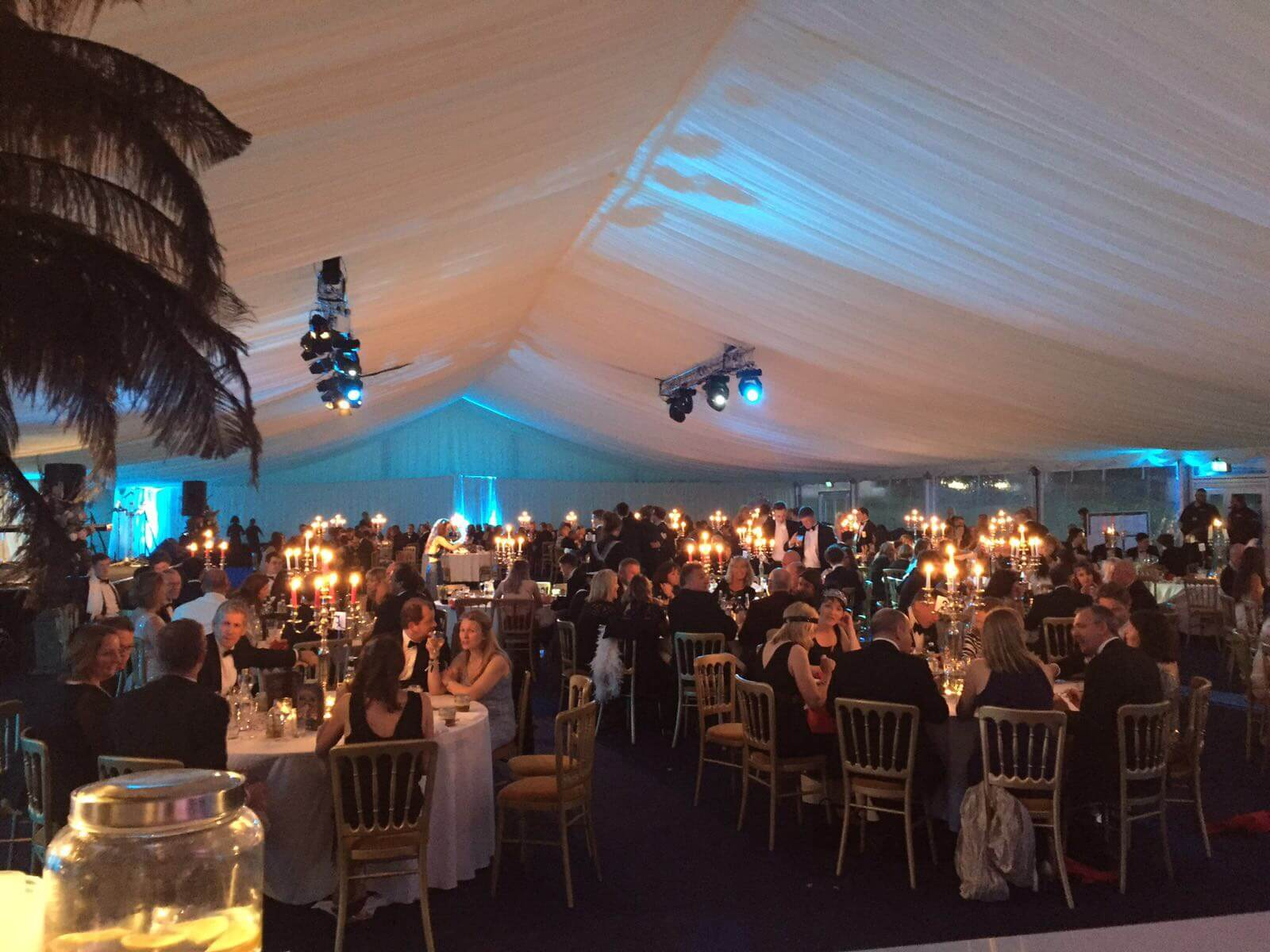 Evening sets in, candelabras glow and blue lights shine from the roof of the marquee making for a majestic setting