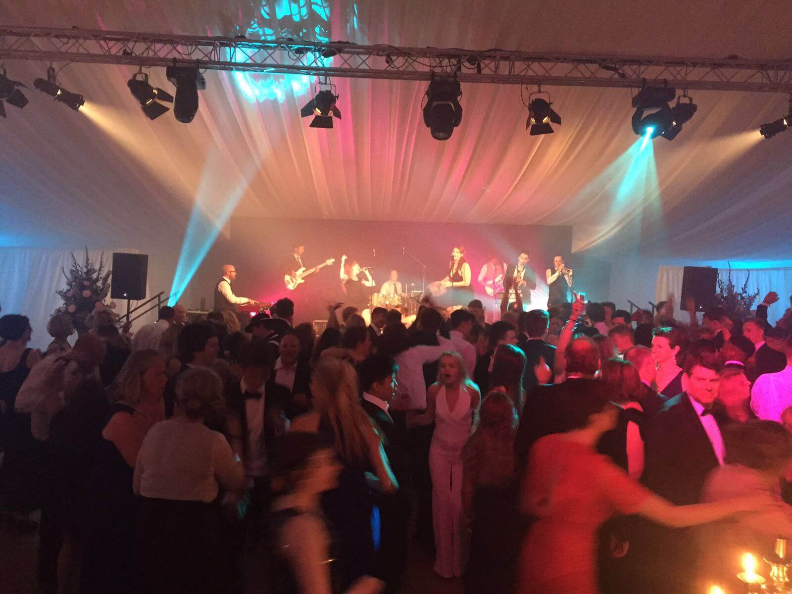 Guests dancing on a parquet dance floor, beneath disco lights in our funky marquee