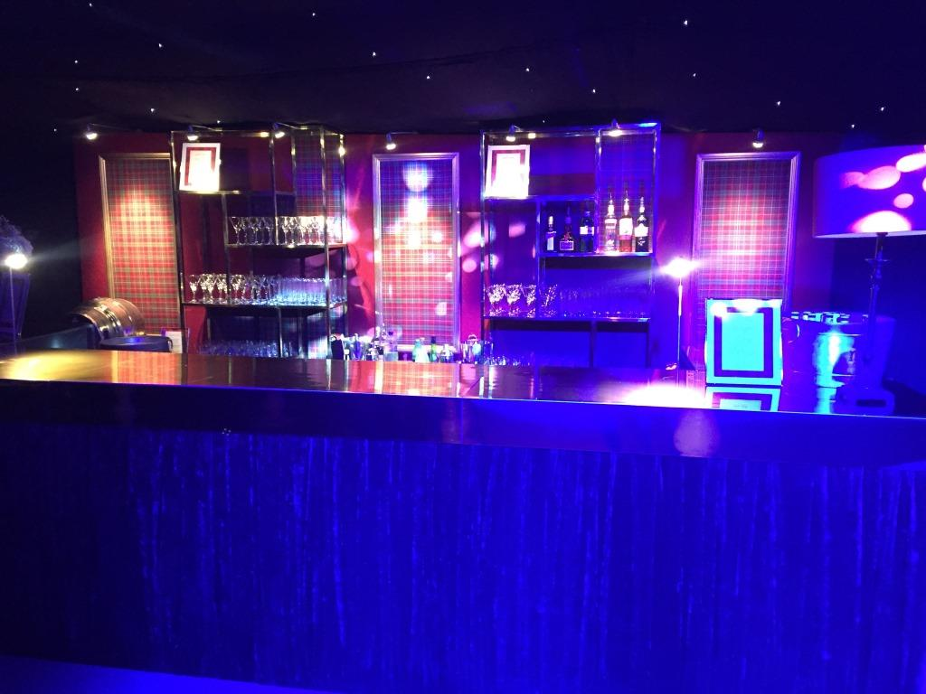 Tartan backdrop and velvet drapes at the front makes for a super stylish bar