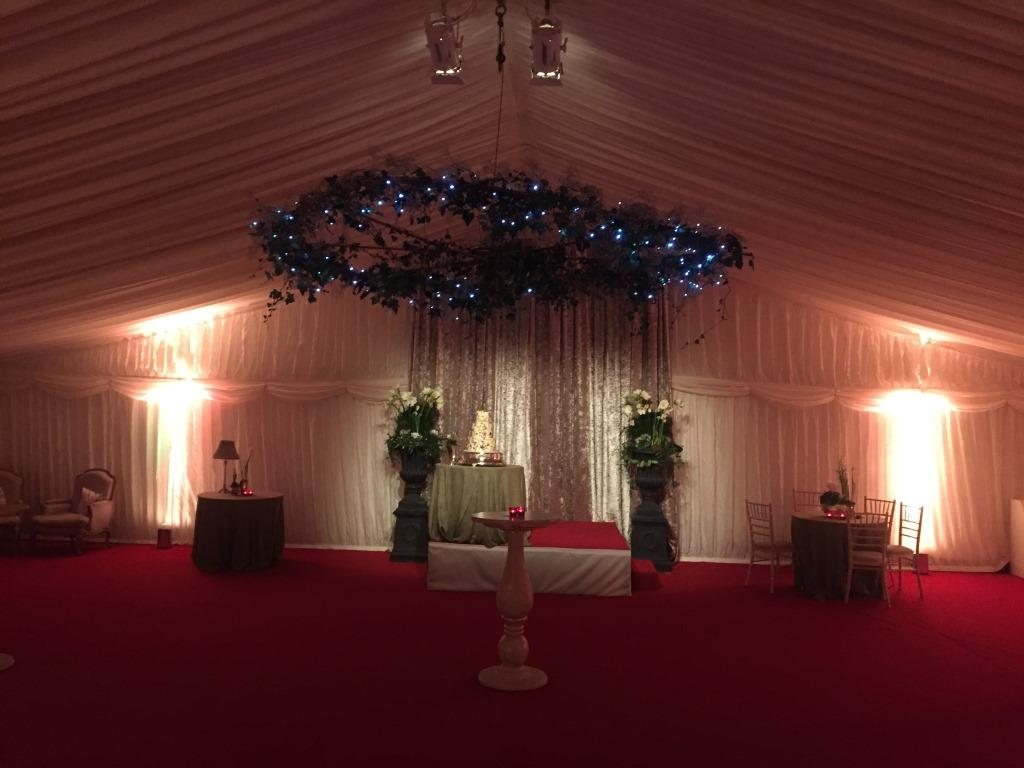 Ivory pleated wall linings and a dark red floor for a stylish wedding reception area