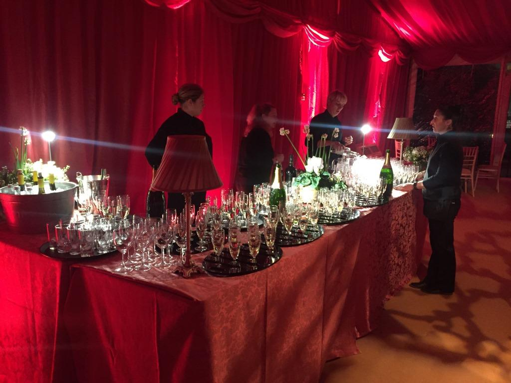 Ready to serve guests Champagne, with burgundy linings draped all around the wedding marquee