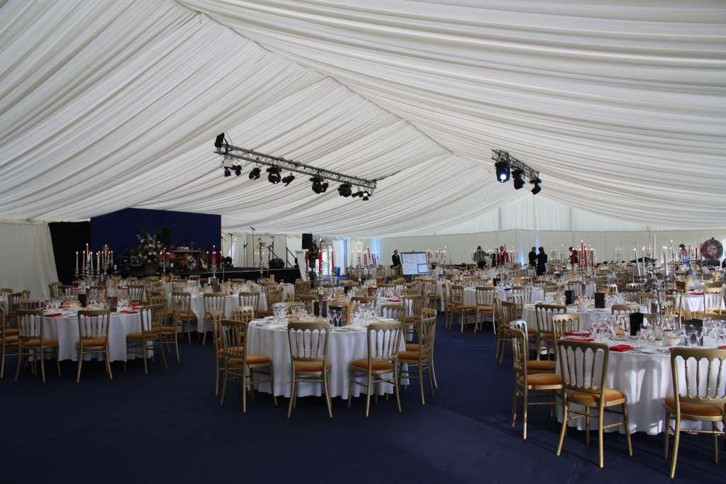 Ivory pleated marquee with round tables and Cheltenham chairs, ready for the ball to begin