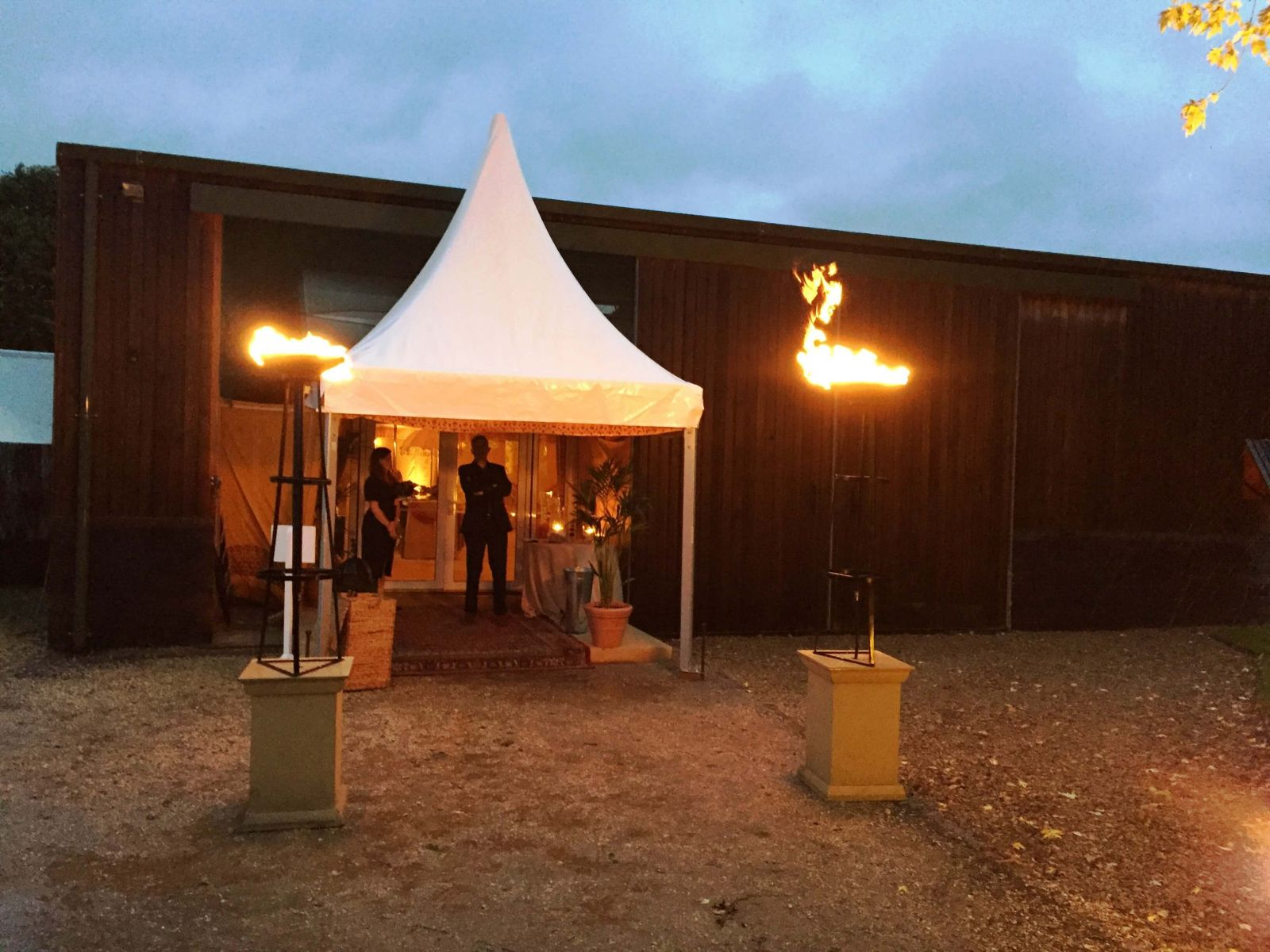 Fiery flambes make this marquee entrance stand out, for this Birthday party in the South West