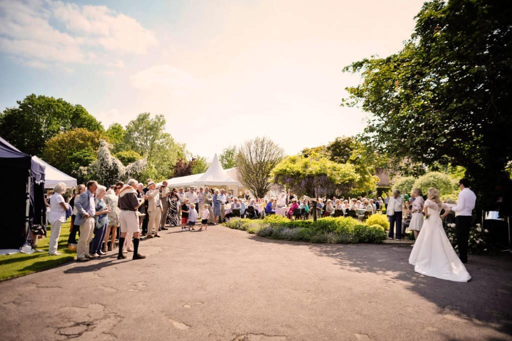 Guests celebrate the newlyweds at this marquee wedding at The Grange Belluton, Bristol