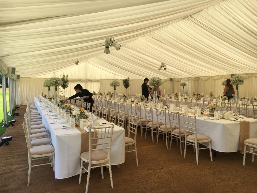 Trestle tables are laid and the finishing touches are made, for this exquisite wedding marquee at The Downs School, Bristol