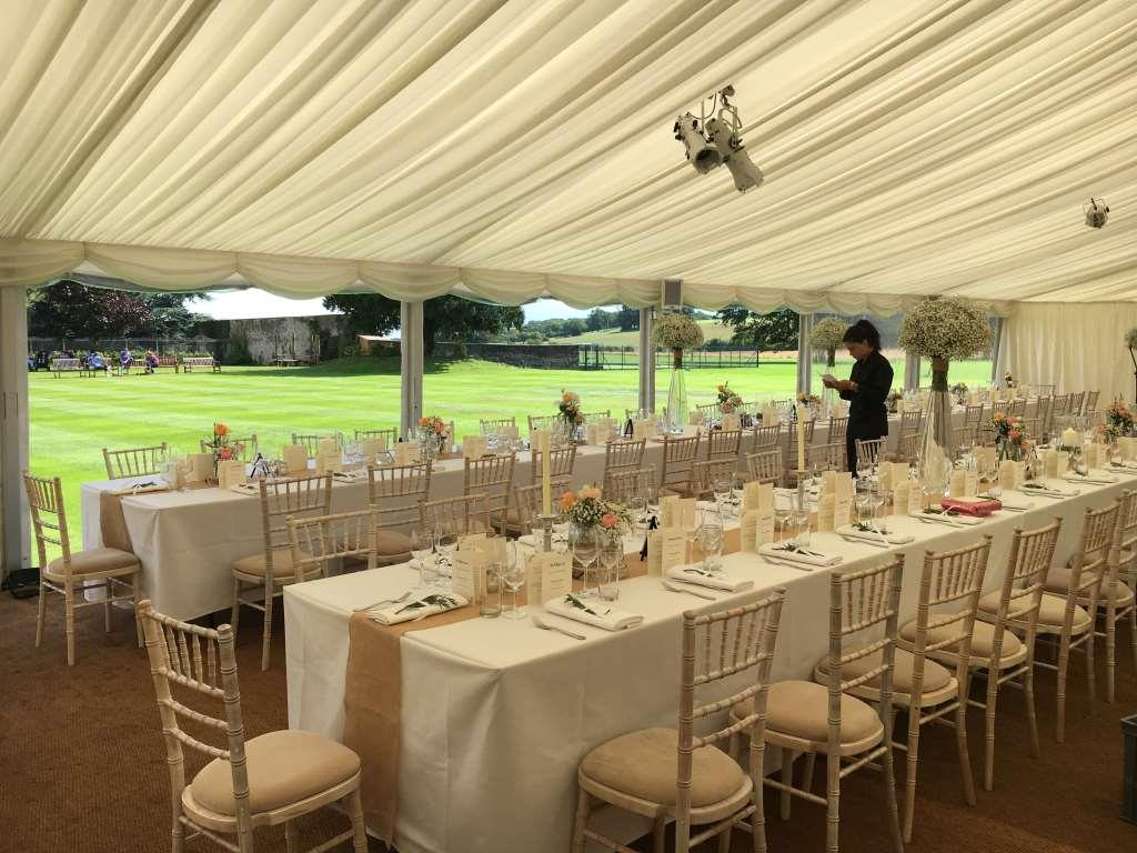 Window walls, ivory pleated linings, Chiavari chairs and long trestle tables