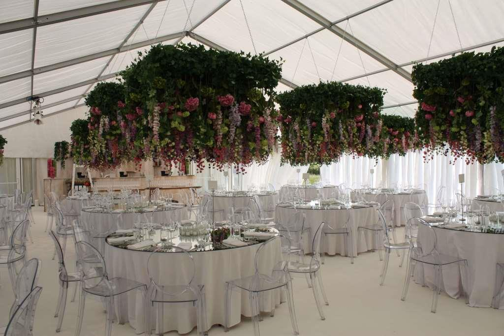 Make the most of the marquee structure by hanging floral decorations from the roof