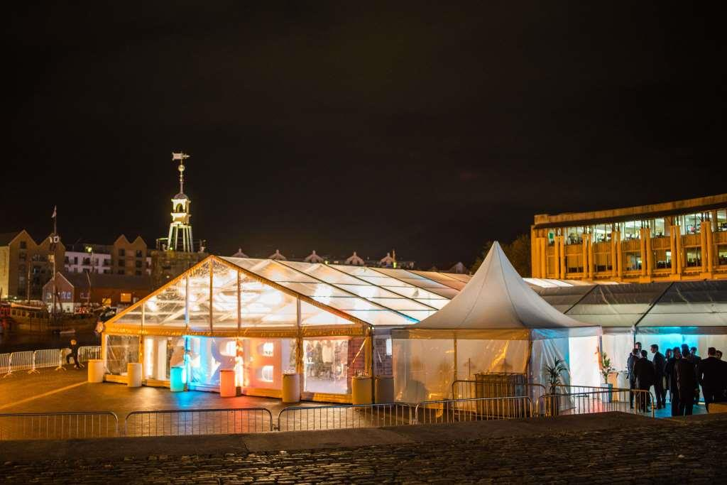 CMC's marquee glowing on the Bristol Harbourside